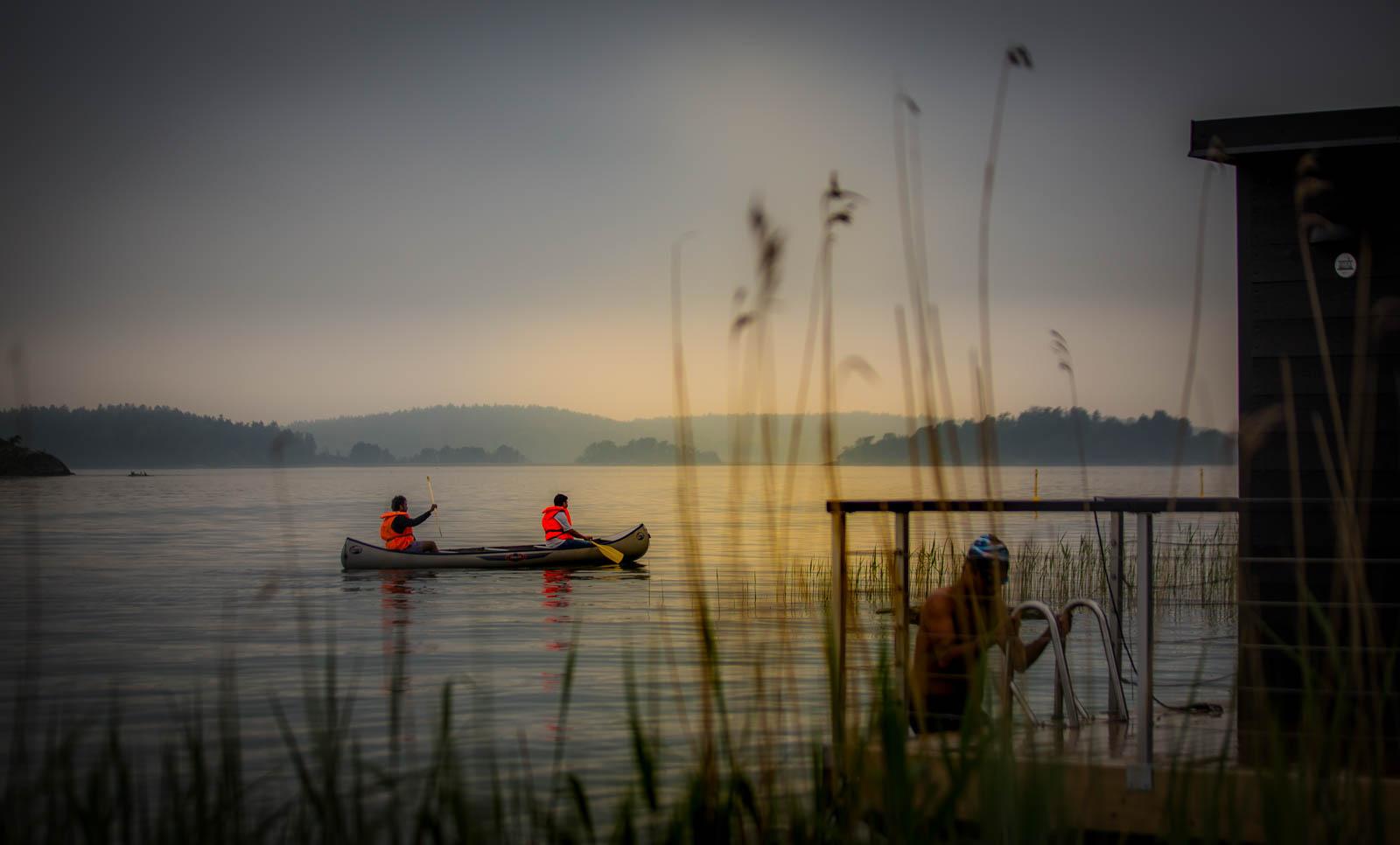 Bild: Magisk kväll vid Almåsa Havshotells Strandhus och havsbastu med bad och kanotpaddlare i solnedgång