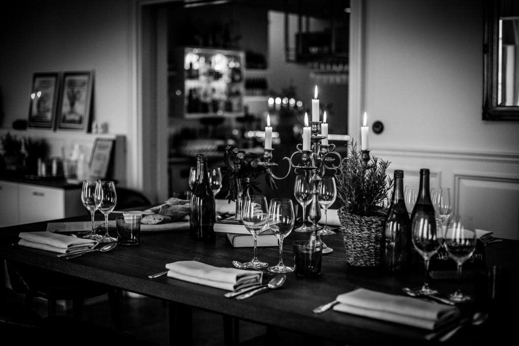 Dukning vid vårt nya barbord, ett tänt kandelaber, vinglas och bestick