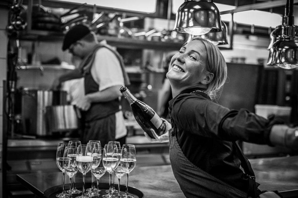 Glada miner i köket - Elin häller Champagne i köket med ett skratt