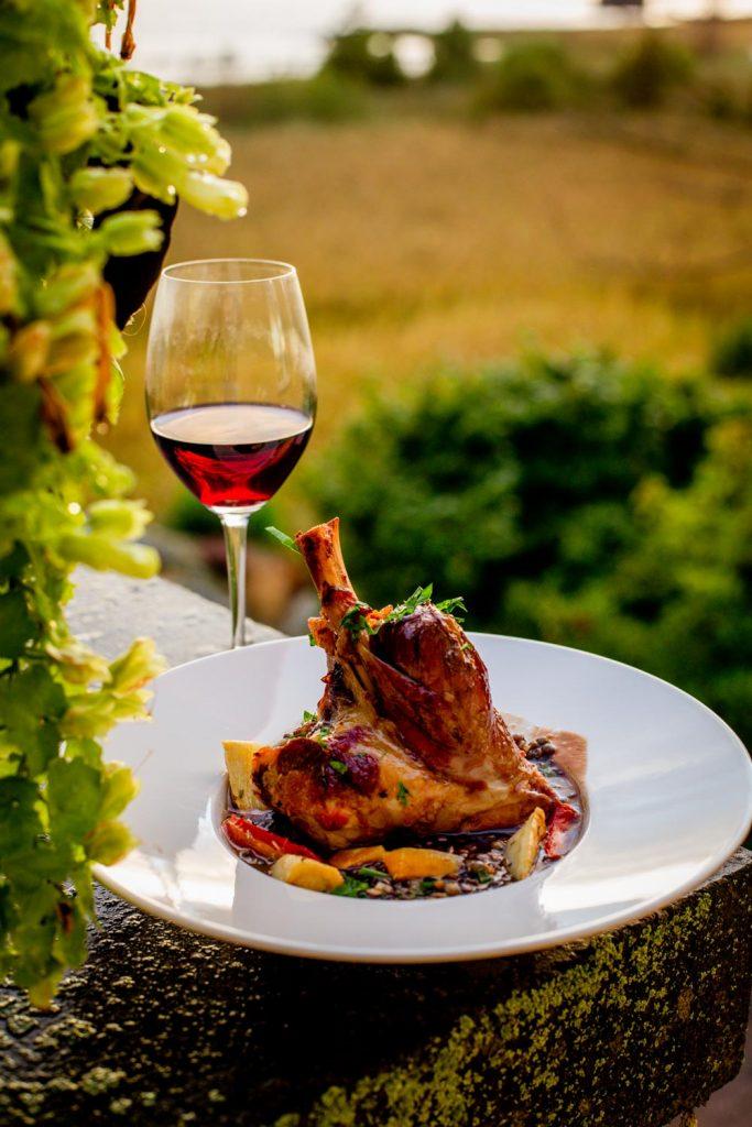Lammlägg bakat över natten på en bädd av linser och frästa grönsaker. Maten och ett glas vin står på en pelare med en växt till vänster, det är solnedgång och himlen är vacker med Hårsfjärden i bakgrunden