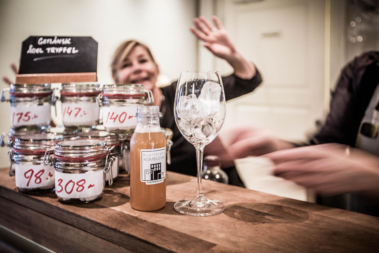 Bild: Ett glas Kombucha vid bardisken med glad hotelldirektör i bakgrunden