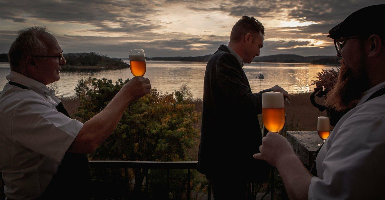 Bild: Njutfullt ögonblick med Norbert Lang och kockar som provar öl vid terrassen med kvällsutsikt över Hårsfjärden