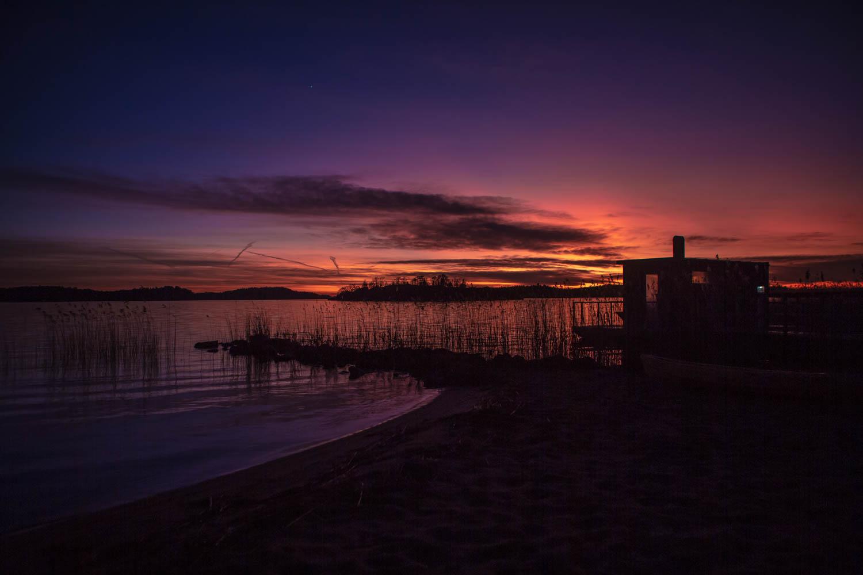 Röd och blå solnedgång med havsbastu och vass i förgrunden