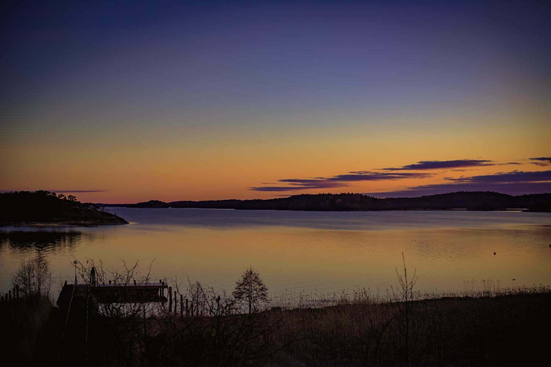 Bild över solnegång över Hårsfjärden med orangea och mörkblå himmel.